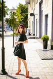 Beautiful woman in a dark stylish dress. Portrait of a fashionable girl