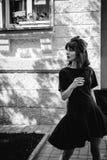 Beautiful woman in a dark stylish dress strolls along . Portrait of a fashionable girl Stock Image