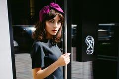 Beautiful woman in a dark stylish dress strolls along . Portrait of a fashionable girl Stock Photography