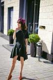Beautiful woman in a dark stylish dress strolls along the street, near boutiques