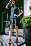 Beautiful woman in a dark stylish dress strolls along . Portrait of a fashionable girl