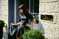 Beautiful woman in a dark stylish dress strolls along . Portrait of a fashionable girl Royalty Free Stock Photos