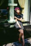 Beautiful woman in a dark stylish dress strolls along street, near boutiques. Portrait of a fashionable girl
