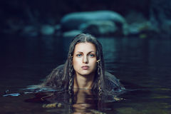 Beautiful woman in dark water stream Royalty Free Stock Images