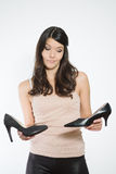 Beautiful woman deciding between two shoes Royalty Free Stock Photography
