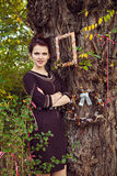 Beautiful woman by decorated autumn tree Royalty Free Stock Image