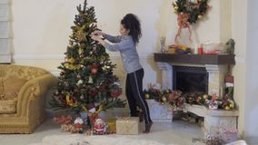 Beautiful woman decorates Christmas tree. She hangs two red toys on a branches of fir tree. The room and fireplace decorated with a garlands and toys stock video