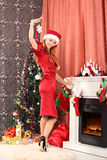 Beautiful woman decorating the Christmas tree Royalty Free Stock Photography