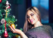 Beautiful woman decorating christmass tree Stock Images