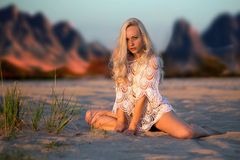 Beautiful woman in desert in white web Royalty Free Stock Photography