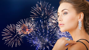 Beautiful woman with diamond earring over firework Stock Photos