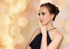 Beautiful woman in diamond jewelry over lights Stock Photography