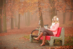 Beautiful woman with digital tablet. Autumn time people outside. Beautiful woman with digital tablet. Young lady sitting on the bench and wearing autumnal Stock Photography