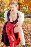 Beautiful woman in a dirndl in an autumn park Royalty Free Stock Photo