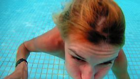 Beautiful woman is diving underwater in water pool. Beautiful woman picturesquely dives underwater in swimming pool. Fun and cute recreation slow motion shot of stock video