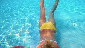 Beautiful woman is diving underwater in water pool. Beautiful woman is diving underwater in swimming pool. Fun and cute recreation shot of woman with a good stock video