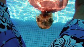 Beautiful woman is diving underwater in water pool. Beautiful woman is diving underwater in swimming pool and swims between her boyfriend legs. Fun and cute stock video footage