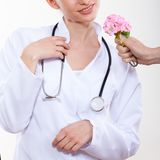 Beautiful woman doctor with a flower. Royalty Free Stock Photos