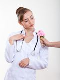 Beautiful woman doctor with a flower. Royalty Free Stock Photography