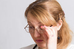 Beautiful woman doctor in glasses, looking down, thinking Royalty Free Stock Photography