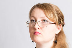 Beautiful woman doctor in glasses, looking up, thinking Stock Image
