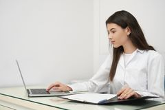 Young woman, doctor working with notebook in clinic. royalty free stock images