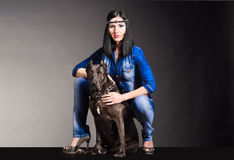 Beautiful woman with a dog. Beautiful woman in jeans clothes sitting next to the dog Stock Photos