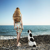 Beautiful woman with a dog on the beach Stock Image