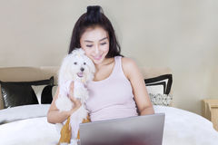 Beautiful woman with dog on the bed Stock Images