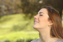 Beautiful woman doing breathing deep exercises in a park. Beautiful happy smiling woman doing breathing deep exercises in a warmth park green background royalty free stock images
