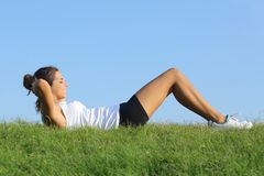 Beautiful woman doing crunches on the grass with the sky in the background Stock Images