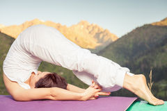 Beautiful woman doing difficult exercise of yoga outdoor Royalty Free Stock Images