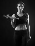 Beautiful woman doing dumbbell curl. Photo of an attractive female doing a dumbbell curl black and white version Royalty Free Stock Photo