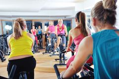 Beautiful woman doing exercise in a spinning class Stock Photos