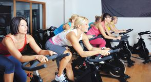 Beautiful woman doing exercise in a spinning class. Beautiful women doing exercise in a spinning class at gym stock image