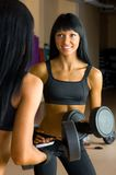 Beautiful woman is doing exercises with the bar Stock Photo