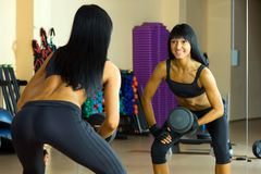 Beautiful woman is doing exercises with the bar Stock Image