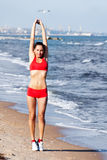 Beautiful woman doing exercises. On the beach Stock Photography