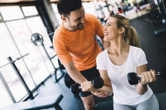 Beautiful woman doing exercises in gym with personal trainer. Beautiful women doing exercises for biceps in gym with personal trainer Stock Photography