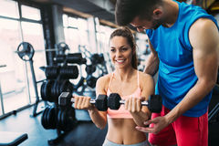 Beautiful woman doing exercises in gym with personal trainer Royalty Free Stock Image