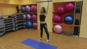 Beautiful woman is doing exercises with sports stick. stock video footage