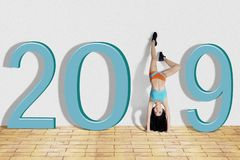 Woman doing handstand exercise with number 2019 royalty free stock images