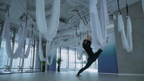 Beautiful woman doing leg stretching puts one leg in hammock for yoga and another on the floor in studio indoors. Many white empty hammocks around. ityscape stock footage