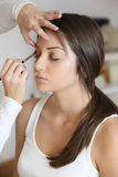 Beautiful woman doing make-up on face Royalty Free Stock Photography