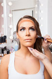 Beautiful woman doing make-up on face Stock Image