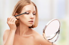 Beautiful woman doing  makeup with brush in the mirror Stock Images