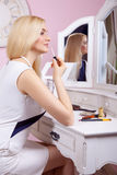 Beautiful woman is doing makeup in front of mirror. Royalty Free Stock Photo