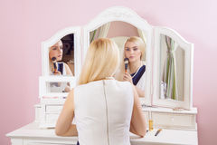 Beautiful woman is doing makeup in front of mirror. Royalty Free Stock Image