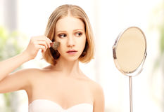 Beautiful woman doing  makeup  in the mirror Stock Image