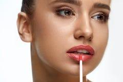 Beautiful Woman Doing Makeup Using Lip Gloss On Lips. Cosmetics Royalty Free Stock Photography